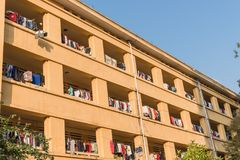 Facade of apartment and dormitory sun drying hanging clothes lin. Low angle view of university dorm with sun drying hanging clothes line in dense of apartments Stock Photography