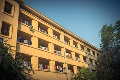 Facade of apartment and dormitory sun drying hanging clothes lin. Low angle view of university dorm with sun drying hanging clothes line in dense of apartments Stock Image