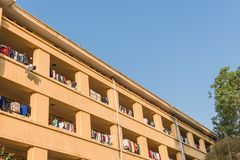 Facade of apartment and dormitory sun drying hanging clothes lin. Low angle view of university dorm with sun drying hanging clothes line in dense of apartments Stock Photo