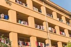 Facade of apartment and dormitory sun drying hanging clothes lin. Low angle view of university dorm with sun drying hanging clothes line in dense of apartments Royalty Free Stock Images