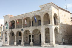 Facade with arches Zamora. Facade of the police station of Zamora in Spain, with some balconies and arches as a gateway. There are some flags royalty free stock photo