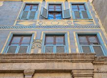Facade of Beit house El Harrawi historic house, Cairo, Egypt. Facade of Beit house El Harrawi with glass windows, wooden grids and ornate wall painted in yellow Royalty Free Stock Images