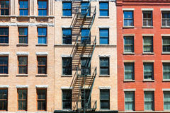 Facade of brick building with fire ladders. Royalty Free Stock Photos