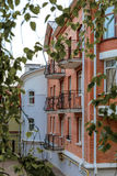 The facade of brick houses with wrought-iron balconies on background of green leaves Stock Photo