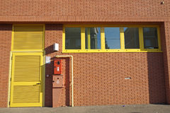Facade of brick industrial building with door and hidrant.  Stock Photography