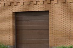 Facade of a brown garage with a closed gate on a brick wall outside. In green grass stock photos