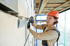 Facade builder plasterer at work. Builder worker works with facade joint of building with plaster and spatula Royalty Free Stock Photo