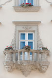 Facade of a building with a balcony and flowers Stock Photos