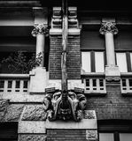 Facade of building in Porta Venezia neighbourhood. Ornamental animal statue hanging from the wall. Architecture is early 1900s nat. Milan, Italy - May 24, 2018 Royalty Free Stock Photography