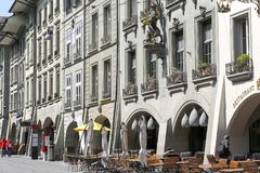 Facade of a building on a street in the old town. Bern, Switzerland - April 20, 2017: There is an outdoor restaurant next to the building. On the facade of this Royalty Free Stock Photography