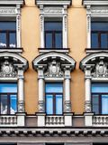 The facade of the building with stucco details in the city of St. Architectural details balconies, pilasters, arches, rosettes, cornices, busts, white patterns stock images