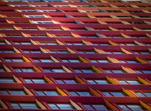 Facade building view of coloured windows frames. Photography on slant coloured windows frames of modern building facade with light reflection giving repeating Stock Photography