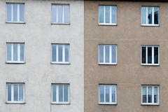 The facade of the building with windows symmetrically divided by color.  Royalty Free Stock Photo