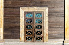 Facade of the building - wooden wall, a door with glass inserts. Ancient architecture stock image
