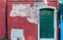 Facade on Burano. Beautiful facade on Burano island, Venice, north Italy. Colorful red house wall with a door and exposed brickwork royalty free stock photo