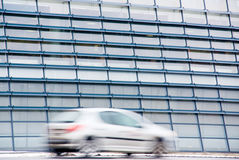 Facade and car. Modern facade with moving car in foreground Stock Images