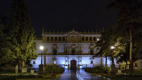 Facade of the Cisneriana University of Alcala de Henares, Spain. On a cold and rainy night with the deserted square and well lit with water reflection Royalty Free Stock Image