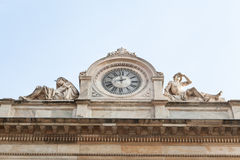 Facade with clock and naked sculptures Stock Photography