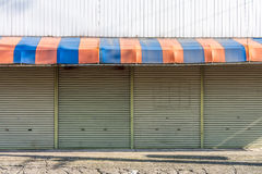 The  facade of closed retail store. There are awning and rolling steel doors of shop front Stock Images