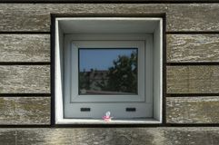 Facade cutout with wooden paneling and small square window with. Pacifier royalty free stock photo