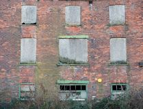 Facade of a derelict abandoned old brick industrial building with broken boarded up decaying windows. Facade of a large derelict abandoned old brick industrial stock photo