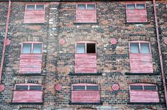 Facade of a derelict abandoned old brick industrial building with red painted broken boarded up windows. Facade of a derelict abandoned old brick industrial royalty free stock images