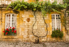Facade with flowers Monpazier. Stone facade with flowers in Monpazier Dordogne France stock image