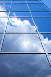 Facade of glass. Modern building in downtown with reflection of sky and clouds Royalty Free Stock Image