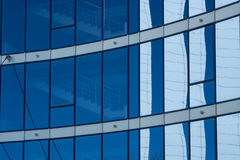Facade glass tower with blue windows. And white reflections on them Stock Image