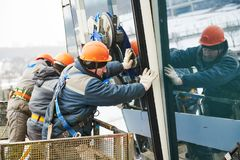 Facade glass window installation. Male industrial builder workers at facade glazing royalty free stock photos