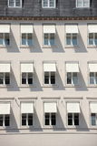 Facade of grey building with  white awning and shade Stock Images