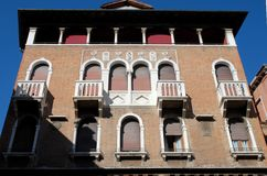 Facade of historical building with three arms and four balconies in Venice. Stock Photos