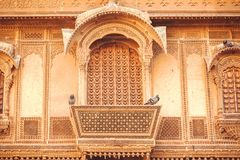 Facade of historical indian house with carved walls, balcony and old design elements, India. Royalty Free Stock Image