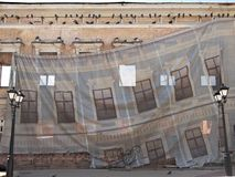 Protective cloth on facade as a curtain in the theater. The facade of the house is closed with a protective cloth during the repair. A banner shows the facade of royalty free stock photography