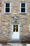Facade of the house with white front door and two windows Royalty Free Stock Photography