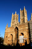 Facade of Lincoln Cathedral. The facade of the amazing Cathedral of Lincoln, UK, in early eavening sun, giving colour to the stone stock photo