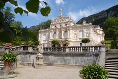 Facade of the Linderhof Castle in Bavaria (Germany). Photo made in Linderhof in Bavaria (Germany). In the picture you see, in the foreground, two green plants Royalty Free Stock Image