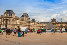 Facade of The Louvre Museum with walking tourists and cars Royalty Free Stock Images