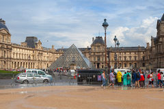 Facade of The Louvre Museum with walking tourists Stock Photo