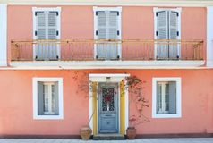 Facade of a lovely greek house with flowers and balcony Stock Photo
