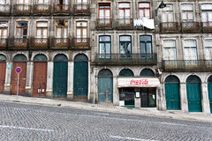 Facade of the lower stories of an apartment house on a steeply sloped cobblestone street in Porto, Portugal Stock Photos