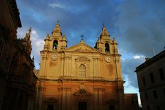 Facade of a Maltese Church. On the island of malta in the mediterranean sea. Sunset lighting under a blue clouded sky Stock Image