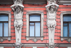 Facade with men statues of an old palace Stock Images