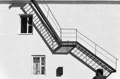 Facade with metal fire staircase. Front view of facade with metal fire staircase and shadow. Black and white geometric composition Stock Images