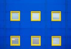 Facade of a modern blue warehouse and six yellow windows Stock Photos