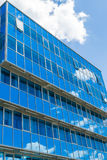 Facade of a modern building. Glass Windows reflected the sky and clouds. Blue gamma Royalty Free Stock Image