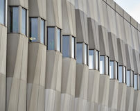Facade of a modern building made of concrete with small windows in cloudy weather. Royalty Free Stock Photography