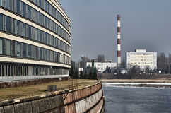 The facade of a modern building in the old river port and chimney power plant. In Poznan Stock Photography