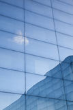 Facade of modern glass building with reflections of blue sky and Stock Image
