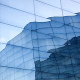 Facade of modern glass building with reflections of blue sky and glass wall Royalty Free Stock Photo